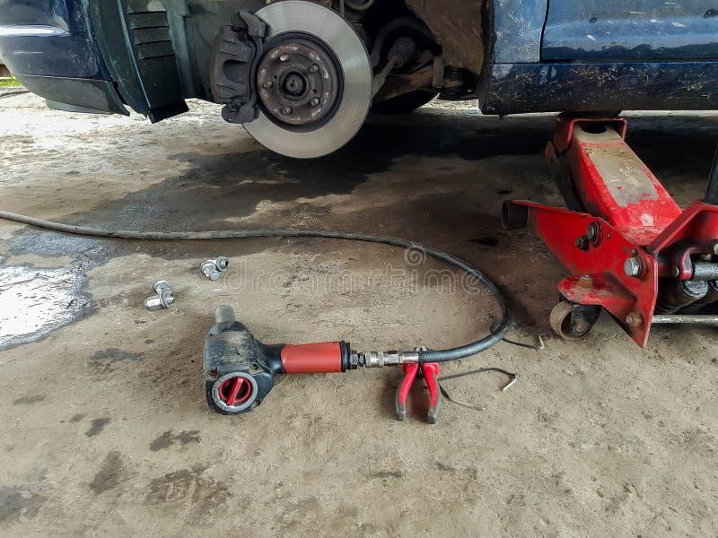 汽车提起与水力插座,在水泥地板,改变的轮胎上的气锤 库存图片