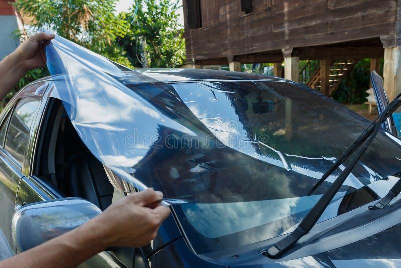 汽车摄制安装wInstalling的车窗色彩,安装挡风玻璃保护影片迷离的汽车影片 库存图片