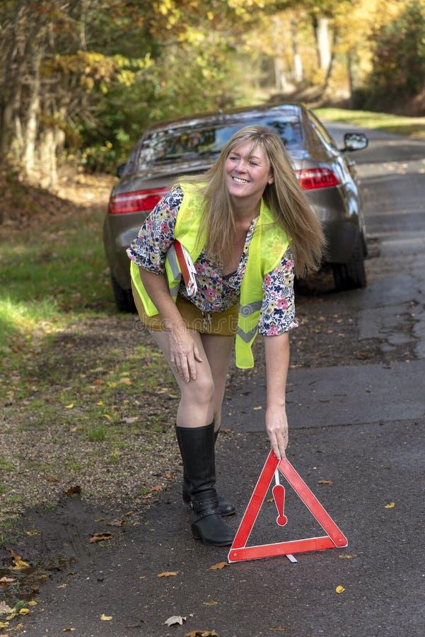 汽车故障 投入一个红色警告三角的妇女司机 免版税库存图片