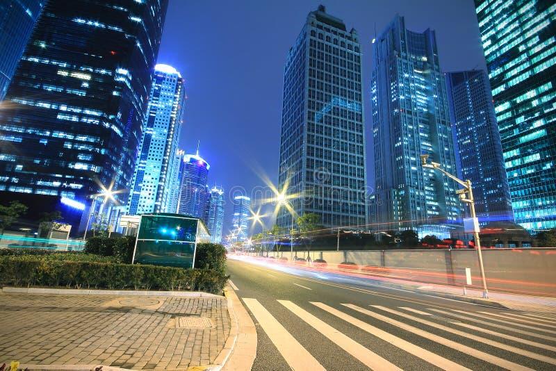 汽车晚上现代办公楼背景与轻的线索的 免版税库存图片