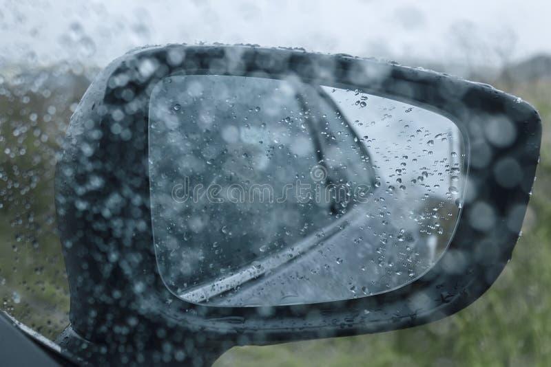 汽车有雨珠的后视镜 免版税库存照片