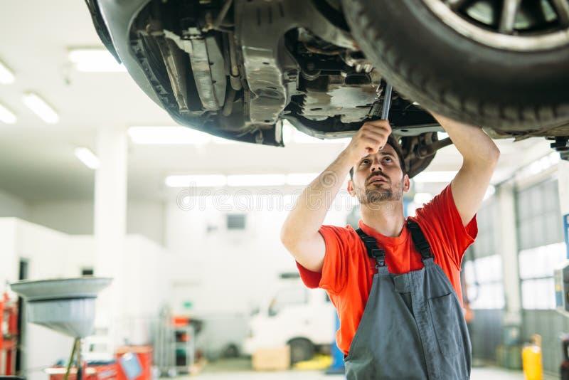 汽车服务、修理、维护和人概念-车间的愉快的微笑的汽车机械师人 免版税库存图片