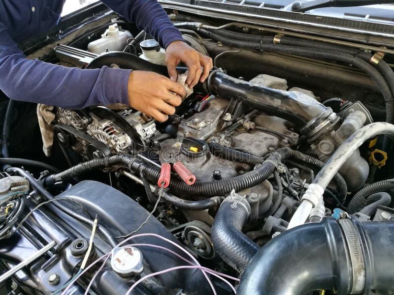 汽车服务引擎,修理,维护的检查,汽车机械师人拉紧了阀门在敞篷汽车,人手定象发动机下 图库摄影