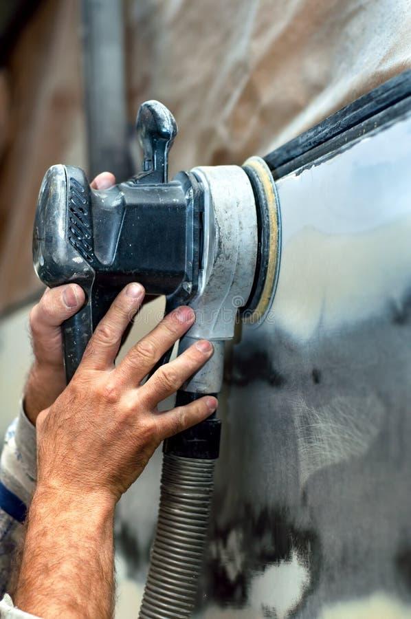 汽车服务,使用力量缓冲机器的汽车机械师 免版税库存照片