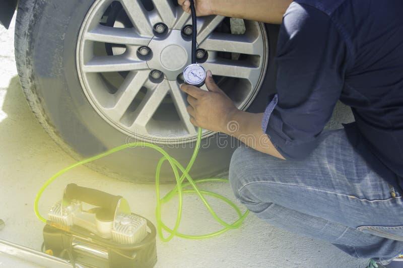 汽车机械师使用车胎压力登记自动服务 库存照片