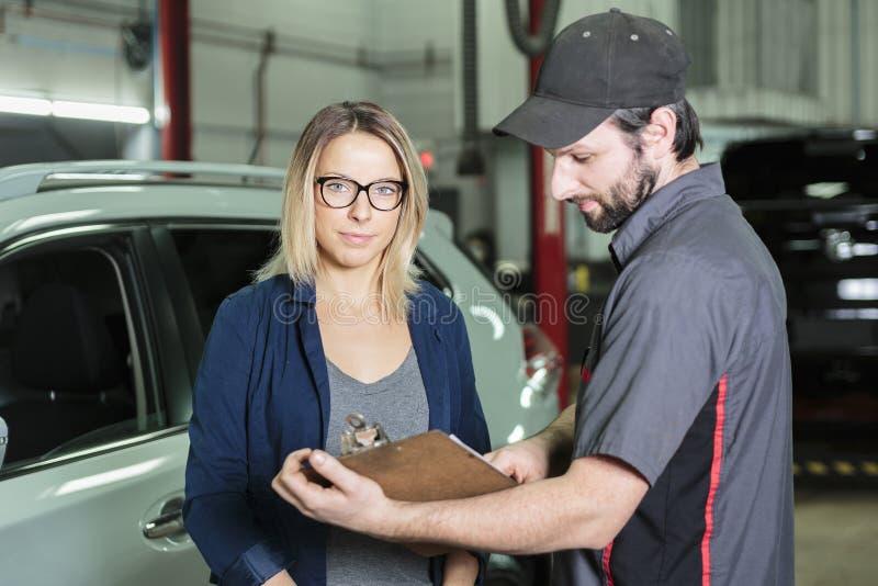 汽车机械师和女性顾客车库的 免版税库存照片