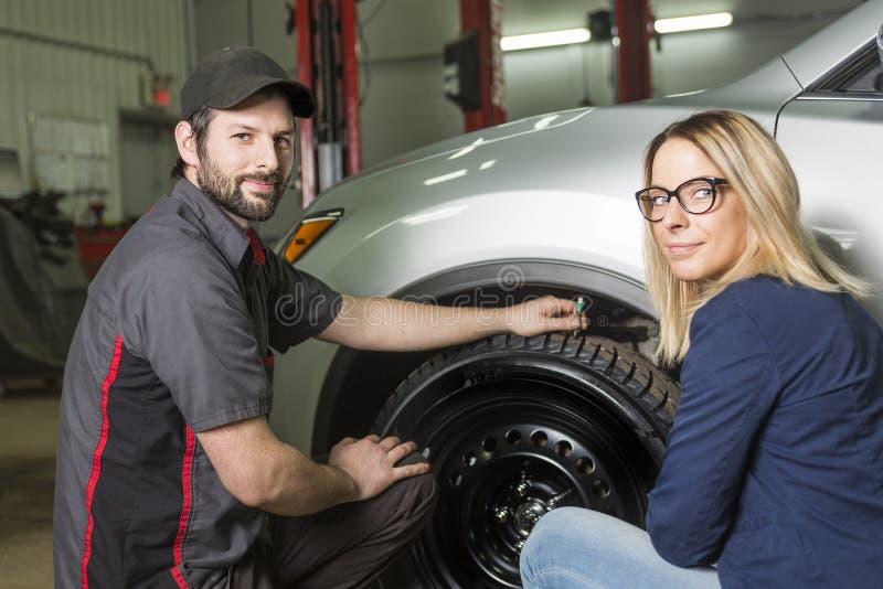 汽车机械师和女性顾客车库的 免版税库存图片