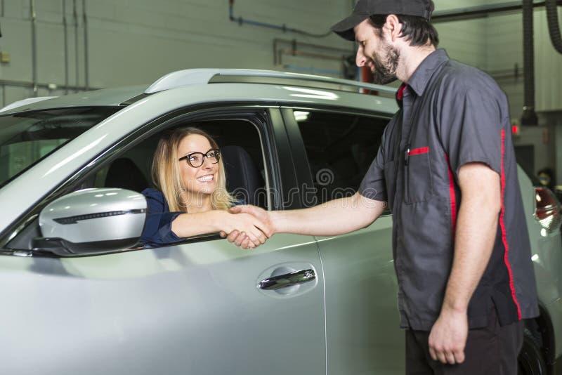汽车机械师和女性顾客车库的 库存照片