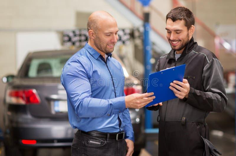 汽车机械师和顾客在汽车商店 免版税库存图片