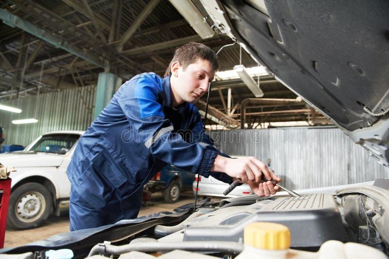 汽车机械师在与板钳一起使用 免版税库存照片