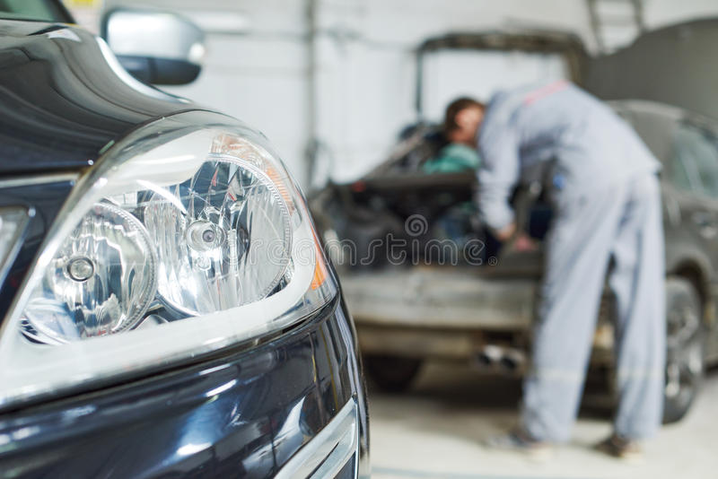 汽车机械师在车库的修理汽车 库存图片