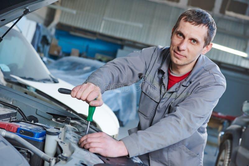 汽车机械师在车库的修理汽车 免版税库存图片