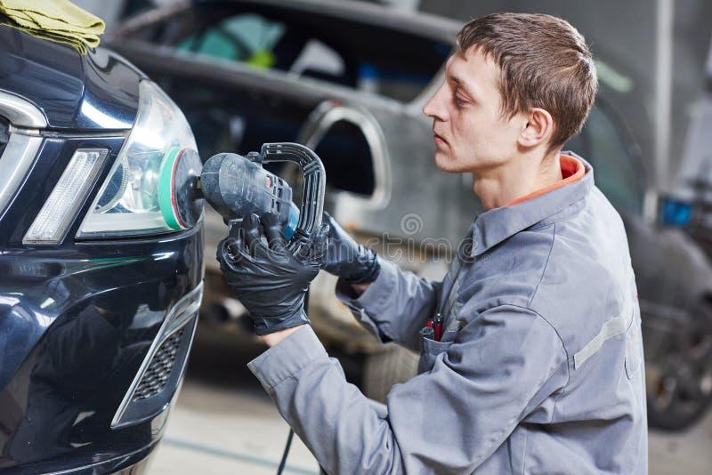 汽车机械师抛光的和擦亮的汽车车灯 免版税图库摄影