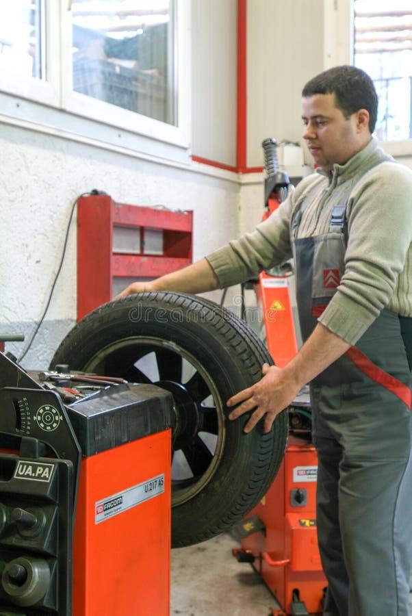 汽车机械师更换在他的车库的一个轮胎 免版税库存照片