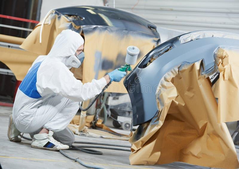 汽车机械师绘画汽车防撞器 免版税库存图片