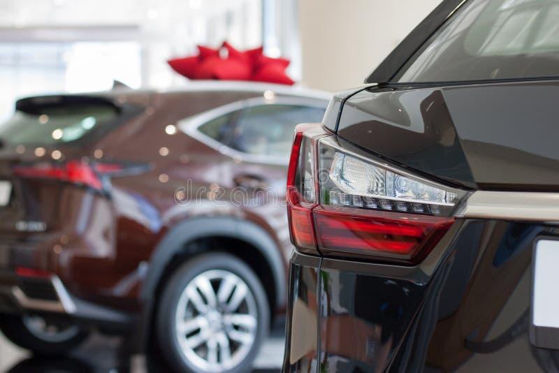 汽车汽车经销权 与bokeh作用的主题的迷离背景 在经销商陈列室的新的汽车 免版税库存照片