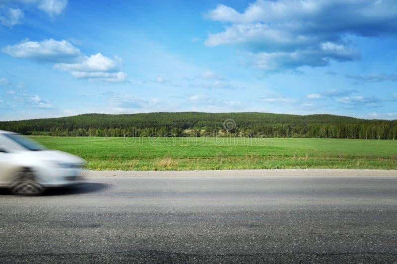 汽车沿乡下公路加速,围拢由森林和蓝天 免版税库存图片