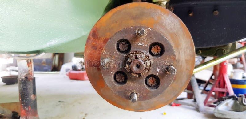 汽车生锈的盘式制动器的关闭修理或维护的在车库 库存照片