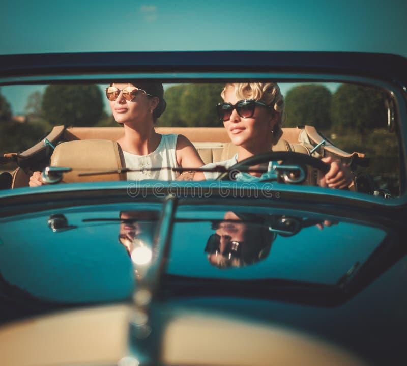 汽车的两个时髦的夫人 库存照片