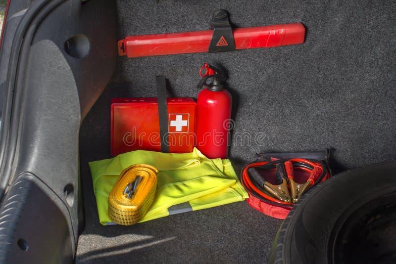汽车的后车箱的内部有急救工具,灭火器,警告三角,反射性背心,星 免版税库存照片