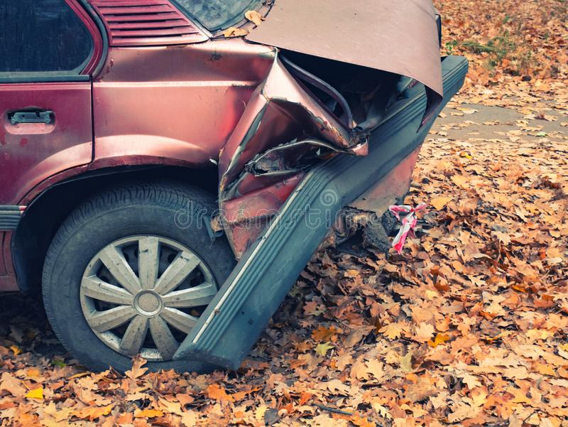 汽车的后面零件在崩溃事故以后的 特写镜头捣毁的被弄皱的后档和泄了气的轮胎边射击  秋天秋天季节 路 免版税图库摄影
