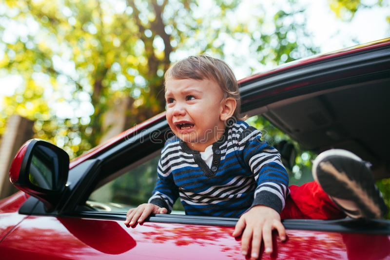 汽车的哭泣的男婴 男孩哭泣并且要离开maniche 免版税库存照片