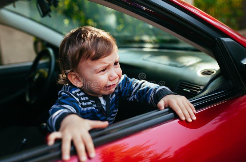 汽车的哭泣的男婴 男孩哭泣并且要离开maniche 免版税图库摄影