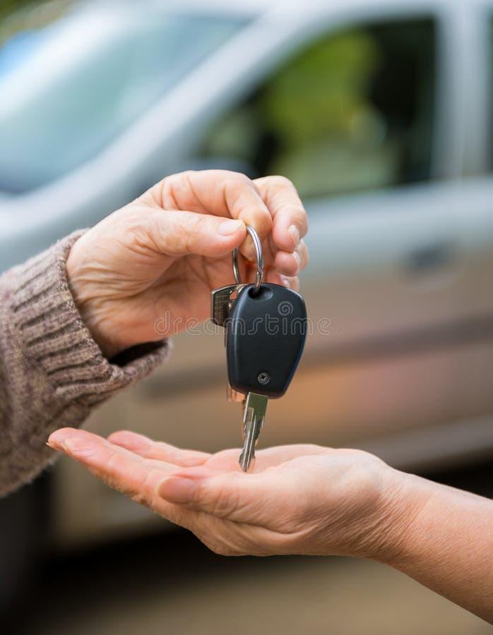 给从汽车的妇女钥匙另一名妇女 免版税库存图片
