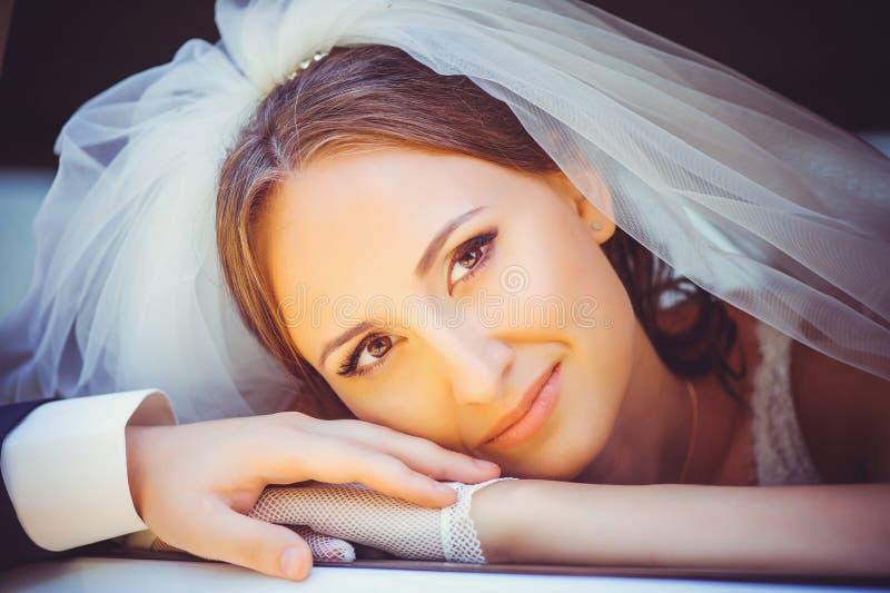 汽车的嫩愉快的新娘,放置她的头在mozhchina的胳膊,在她的hea的白色面纱的婚礼礼服的一名愉快的妇女 免版税图库摄影