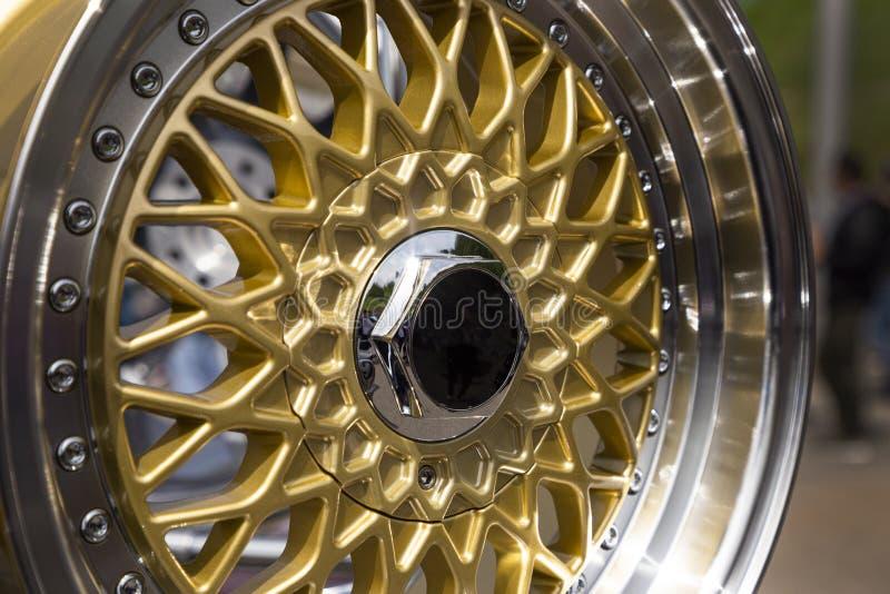 汽车的现代豪华金属合金轮子 与金子色的外缘的陈列室 特写镜头边和正面图 库存照片