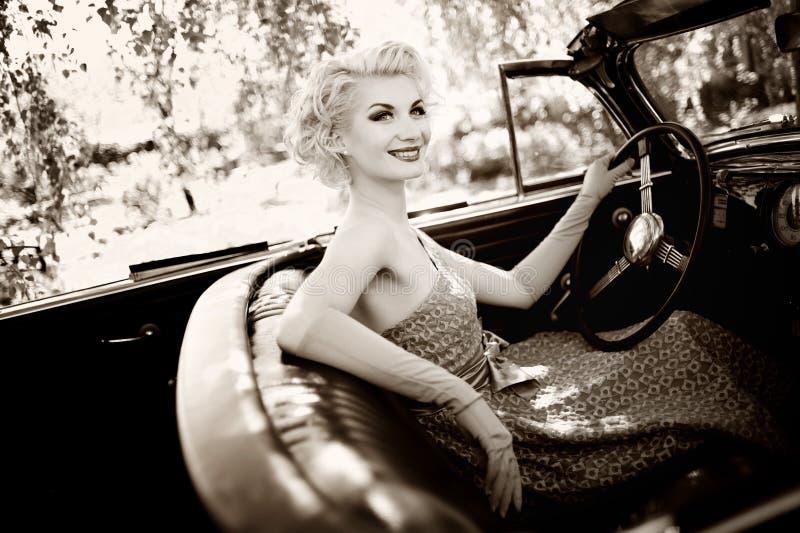 汽车的白肤金发的妇女 库存图片