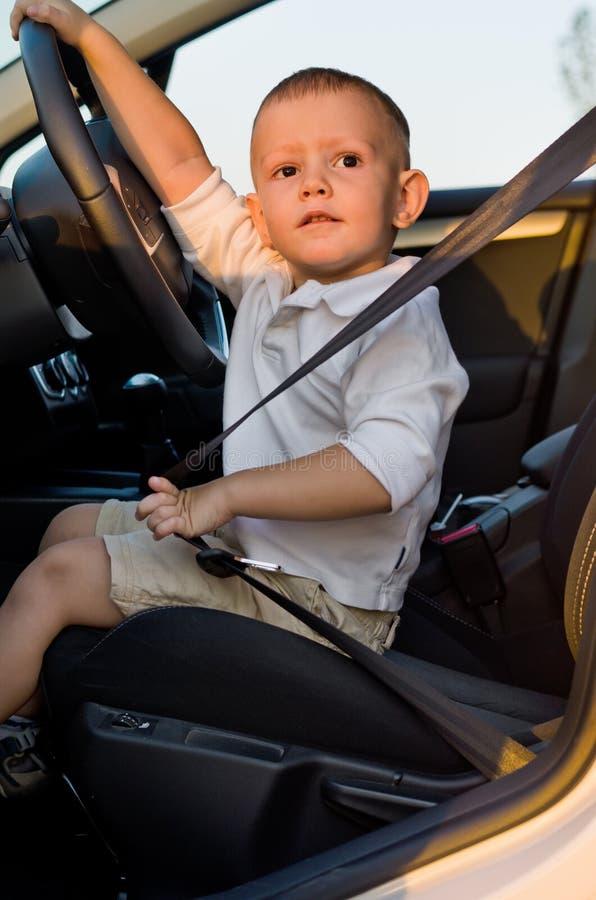 汽车的驾驶席的逗人喜爱的小男孩 库存图片