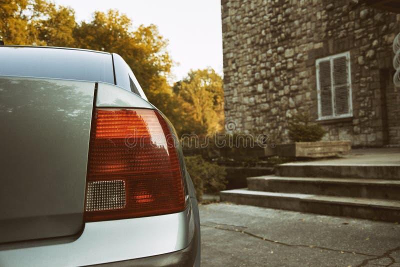 汽车红色背后照明特写镜头与城堡和森林公园背景的 葡萄酒和汽车减速火箭的照片点燃与被定调子的和退色的E-F 免版税库存照片