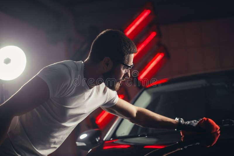汽车详述-人拿着microfiber手中并且擦亮汽车 免版税库存图片