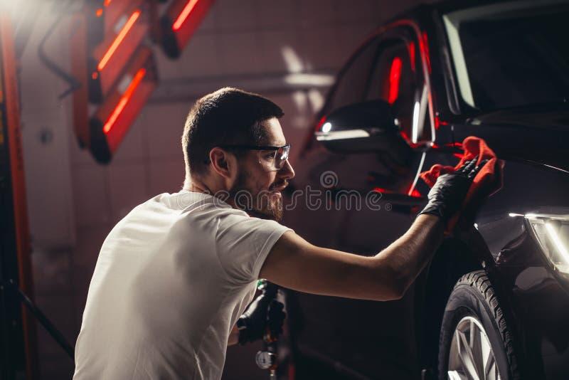 汽车详述-人拿着microfiber手中并且擦亮汽车 图库摄影