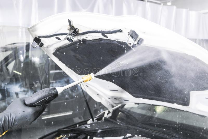 汽车详述 手工洗车引擎用压力水 有水喷管的洗涤的发动机 洗车人工作者清洗的vehi 库存照片