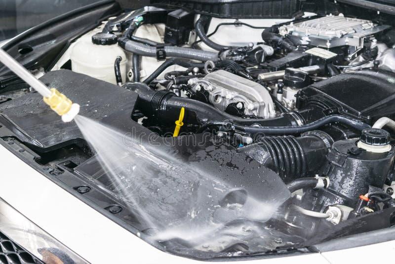 汽车详述 手工洗车引擎用被加压的水 有水喷管的洗涤的发动机 汽车washman工作者清洁澳大利亚 免版税库存图片
