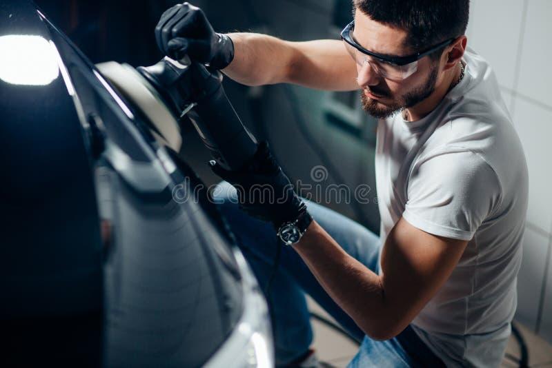 汽车详述-有轨道磨光器的人在汽车修理店 选择聚焦 免版税库存图片