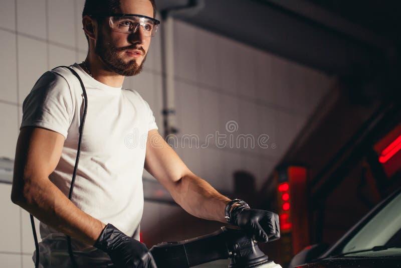 汽车详述-有轨道磨光器的人在汽车修理店 选择聚焦 图库摄影