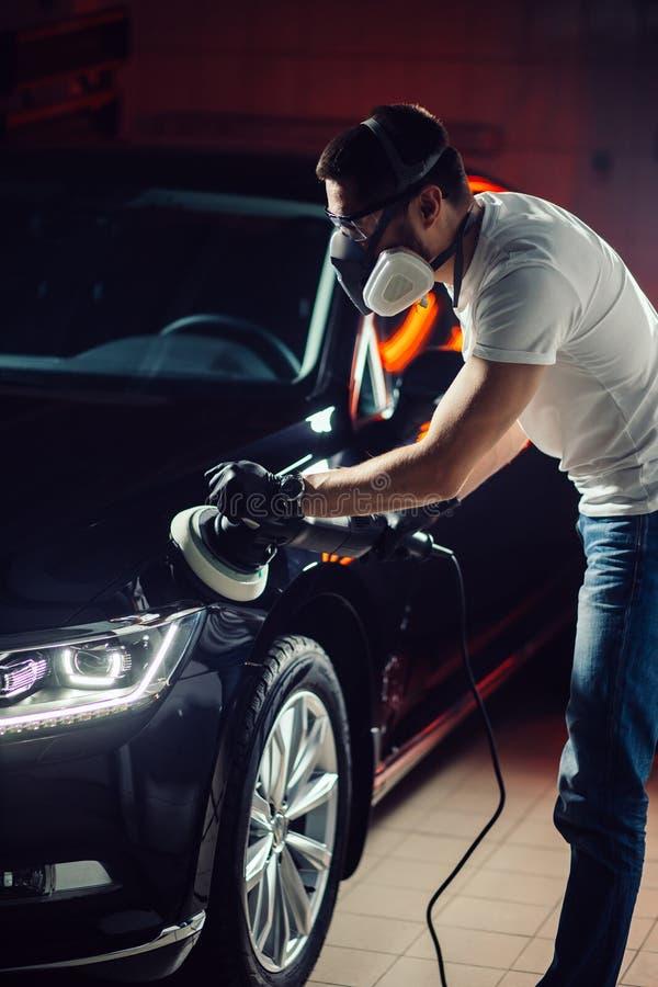 汽车详述-有轨道磨光器的人在汽车修理店 选择聚焦 库存照片