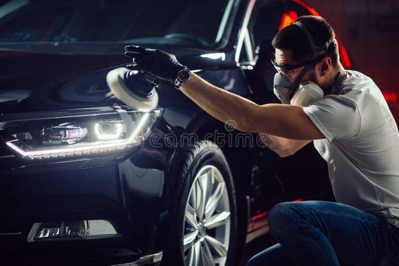 汽车详述-有轨道磨光器的人在汽车修理店 选择聚焦 免版税图库摄影