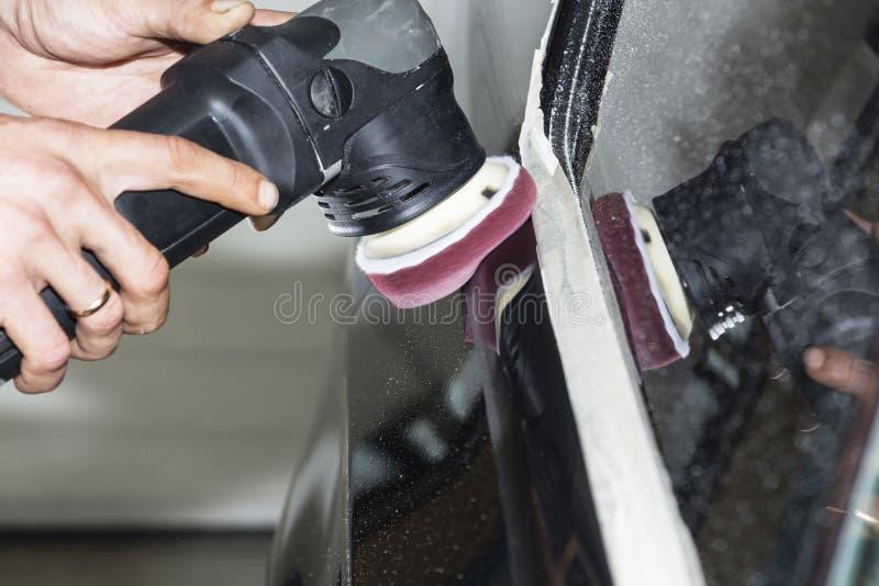 汽车详述-有轨道磨光器的手在汽车修理店 选择聚焦 免版税库存图片