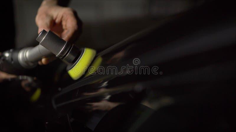 汽车详述-有轨道磨光器的手在汽车修理店 r 汽车擦亮和LCP更正 免版税库存照片
