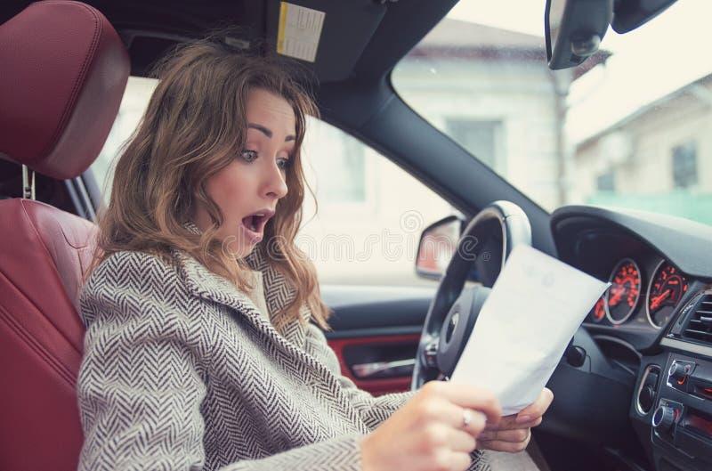 汽车读书保险纸的震惊妇女 免版税库存图片