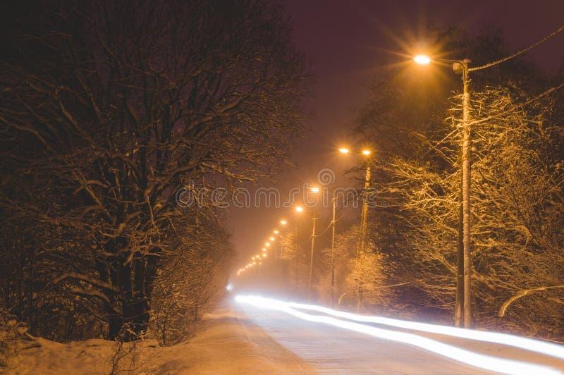 汽车车灯在雪道的在冬天夜之前 免版税库存图片