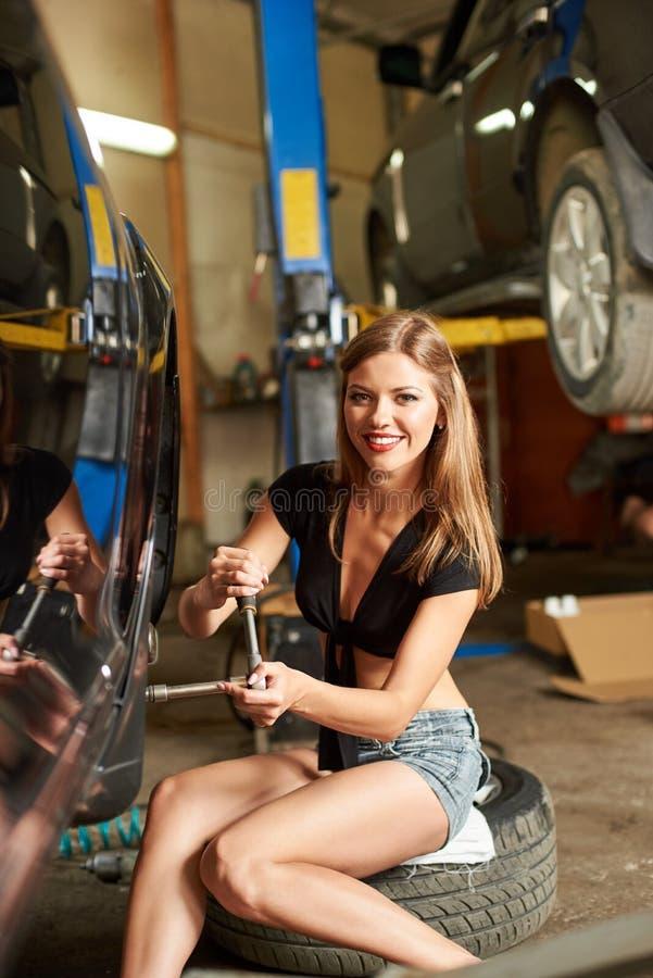 汽车车间,女孩坐轮胎在黑汽车附近 特写镜头 免版税库存图片