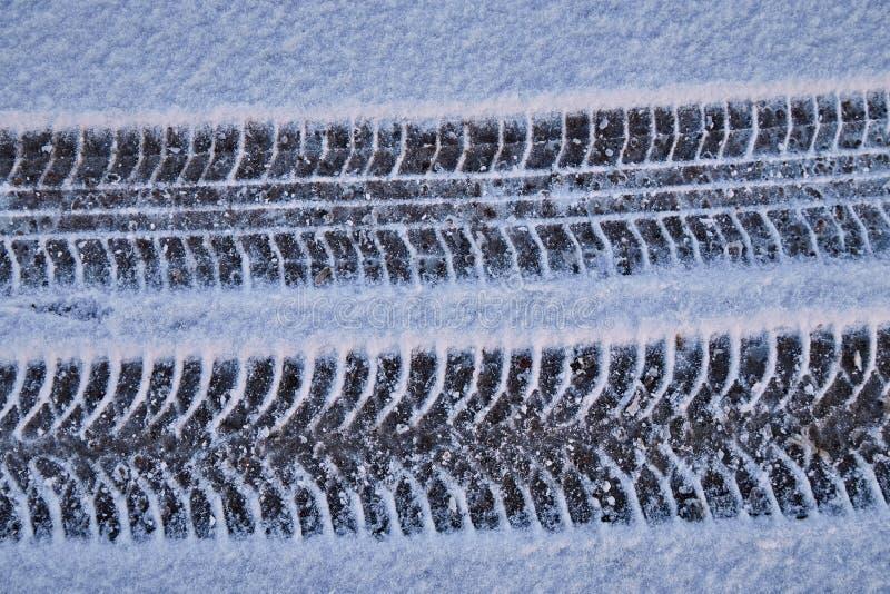 汽车轨道在白色雪的 免版税库存图片