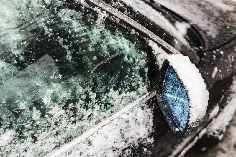 汽车边看法镜子和用冰盖的车窗和雪、窗户清洁、恶劣天气、雪和冰在玻璃,液体 库存图片