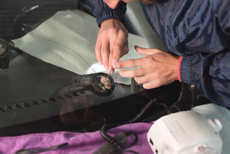汽车釉工作者定象和修理一辆汽车的挡风玻璃或挡风玻璃的关闭在车库服务站的 查询 免版税库存照片