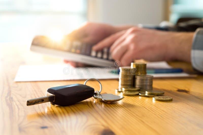 汽车钥匙和金钱在桌上与使用计算器的人 免版税图库摄影